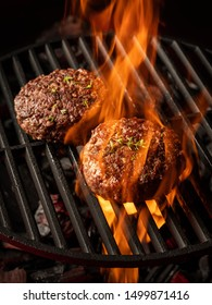 Cooking meat cutlet on hot grill barbecue grate with fire flams and smoke on black background.