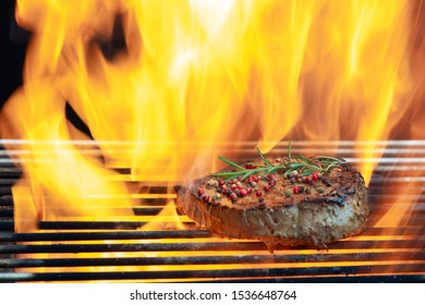 Cooking meat cutlet and  Rosemary Pepper  Salt  on hot grill barbecue grate with fire flams and smoke on black background.