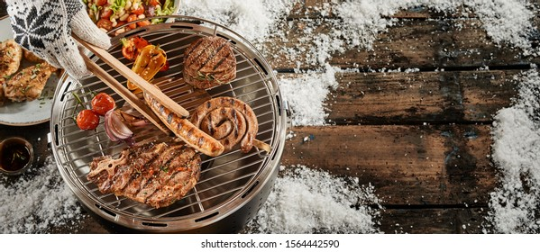 Cooking meat on compact round barbecue grill in winter, viewed from above with copy space on old wooden table surface covered with snow
