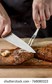 Cooking meat steak with by chef hands on wooden background. Food recipe concept. Vertical food photo.