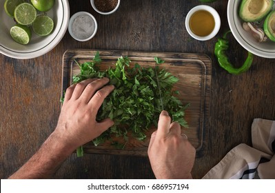Cooking of Mexican guacamole sauce. Man preparing Mexican sauce guacamole, top view