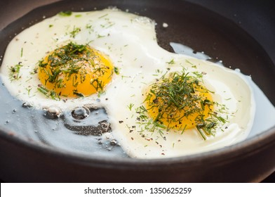 Cooking morning chicken eggs with herbs and seasonings in a black frying pan in sunflower oil