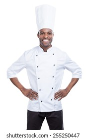 Cooking is my life! Confident young African chef in white uniform holding hands on hips and smiling while standing against white background