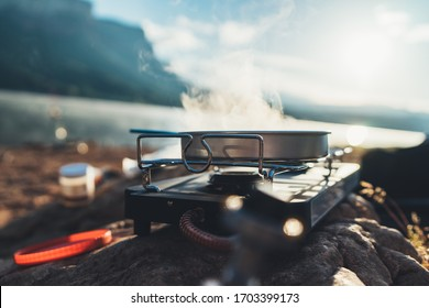 cooking in nature camping outdoor, cooker prepare breakfast picnic on metal gas stove, tourism recreation outside; campsite lifestyle