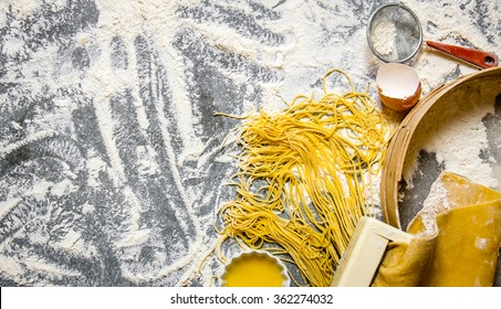 Cooking noodles. The pasta maker with strainer, eggs and flour. On the stone table. Free space for text . Top view