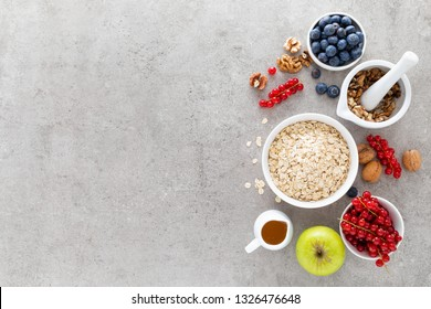 Cooking oatmeal with fresh berries, blueberry, red currant, walnuts and honey. Healthy vegetarian breakfast food concept, top view, flat lay