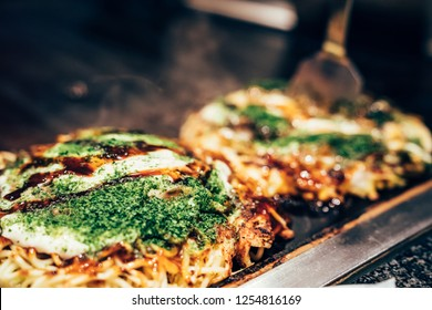 cooking okonomiyaki in local restaurant on teppanyaki pan. delicious Japanese hot plate pizza with green vegetable and sauce on it surrounding by smoke on iron plate indoor.