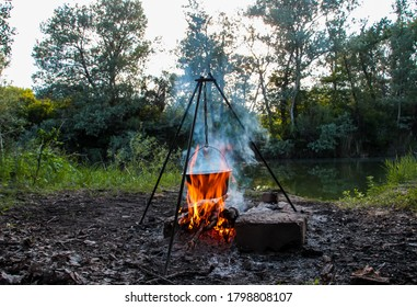 Cooking on a campfire in nature, cooking on a campfire in the campaign. Camp kitchen, cooking in the forest on a fire. Pot on an open fire. The concept of camping life.