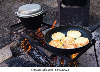 Cooking on a fire in the forest. on the grid are the pot and pan. in a frying pan fried pancakes