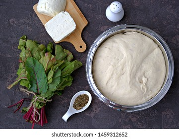 Cooking Ossetian pies with beet tops and cheese, step one. Ready yeast dough, white Suluguni cheese, fresh beet tops, spices, salt. Caucasian cuisine. Top view. Recipe card.