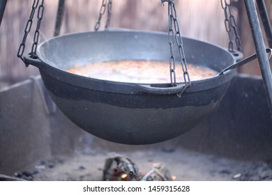 Cooking outside on the fire in a large cauldron.