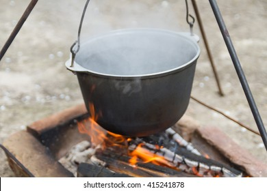 Cooking over a campfire in a cast iron pot. Cast iron pot for soup hanging over the fire campfire. Cooking over a fire in a kettle.