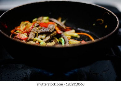 cooking ovoci and meat in a skillet - Shutterstock ID 1202310568