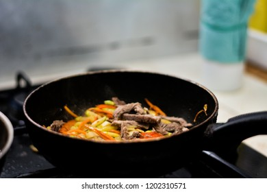 cooking ovoci and meat in a skillet - Shutterstock ID 1202310571