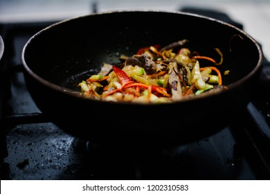 cooking ovoci and meat in a skillet - Shutterstock ID 1202310583