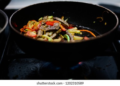 cooking ovoci and meat in a skillet - Shutterstock ID 1202310589