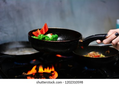 cooking ovoci and meat in a skillet - Shutterstock ID 1202310598