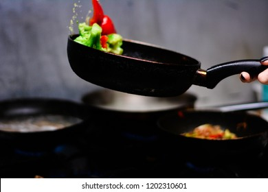 cooking ovoci and meat in a skillet - Shutterstock ID 1202310601