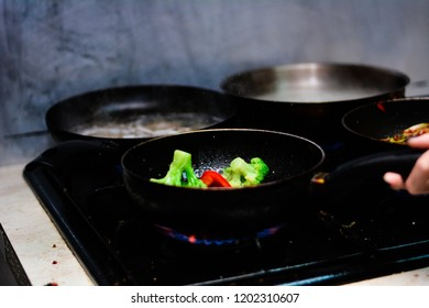 cooking ovoci and meat in a skillet - Shutterstock ID 1202310607