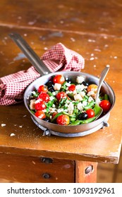 Cooking pan with warm salad with green beans, black olives, croutons, cherry tomatoes, feta cheese and pepper on a wooden table, selective focus. Healthy and organic food option. Vegetarian food.