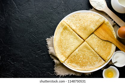 Cooking pancakes for breakfast. Ingredients for making pancakes and fried pancakes on black slate background top view