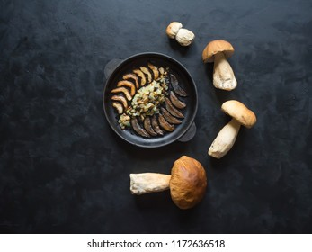 Cooking penny bun. Fried cepes in a iron pan on the black table. Top view.