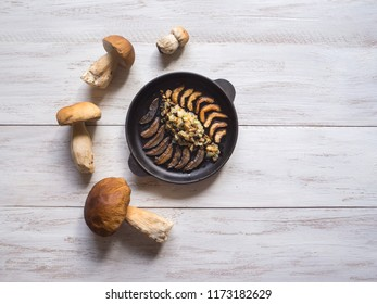 Cooking penny bun. Fried cepes in a iron pan on the white wooden table. Top view.