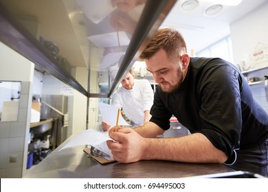 cooking and people concept - happy male chef and cook with grocery lists or bills doing inventory at restaurant kitchen