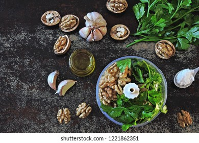 Cooking pesto sauce with walnuts and parsley. Walnut Pesto. Ingredients for walnut pesto in a blender cup. Vegan pesto.