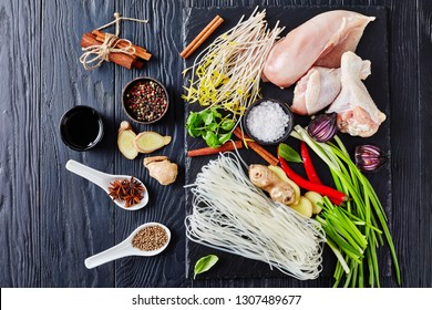 cooking Pho Ga - raw ingredients for asian chicken soup with rice noodles, bean sprouts, onion, herbs and spices on a black slate tray on a table, view from above,  flatlay