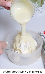 Cooking the pie with mascarpone cream. A woman prepares an impregnation of mascarpone for the cake. Adds condensed milk.
