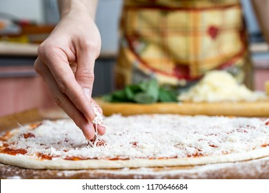 Cooking pizza. arranges cheese ingredients on the dough preform. Closeup hand of chef baker in uniform blue apron cook at kitchen