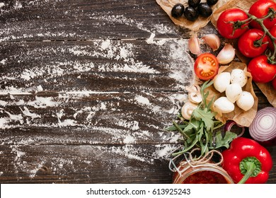 Cooking Pizza. Pizza ingredients on the wooden table with copy space, top view.
