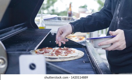 Cooking pizza on outdoor gas grill.