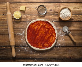 Cooking pizza. Tomato sauce on a raw pizza dough. Top view.