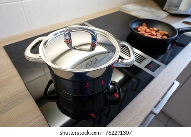 Cooking pot with chrome-plated lid on a cooktop with extractor fan