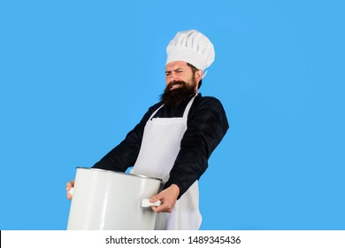 Cooking pot. Cookware, dinnerware, kitchenware. Male chef cook holds big pot. Cooking, culinary. Food, profession and people concept. Saucepan, casserole. Cook man in apron holds saucepan in kitchen.