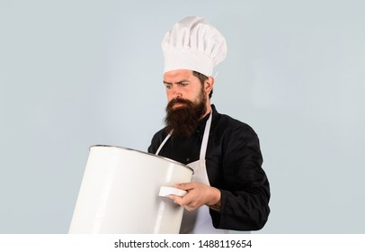 Cooking pot. Male chef cook holds big pot. Cooking, culinary. Food, profession and people concept. Saucepan, casserole. Cook man in apron holds saucepan in kitchen. Cookware, dinnerware, kitchenware.