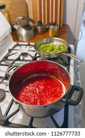 Cooking a pot of red tomato sauce and a pan of green peppers on a gas stove and a jar of hot green chiles