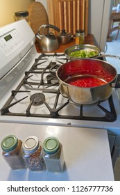 Cooking a pot of red tomato sauce and a pan of green peppers on a gas stove with bottles of herbs and spices nearby