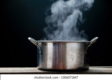 Cooking in pot. steam over the pot on black background.