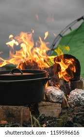 Cooking potatoes wrapped in foil on an open campfire