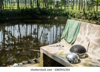 Cooking pots, spoons and a cloth dry on a concrete bench by steps to a pond or ghat in a village in rural Bangladesh.