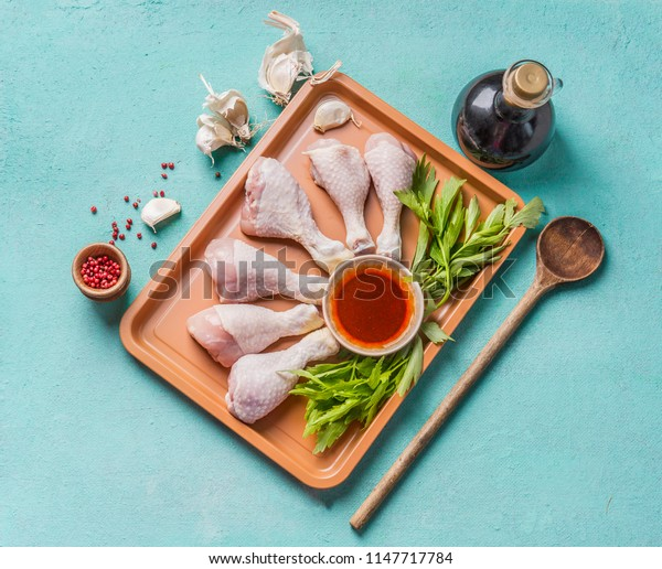 Cooking preparation of raw chicken drumsticks. Raw Chicken legs on plate with herbs, spices , sauce and cooking spoon on light blue background, top view