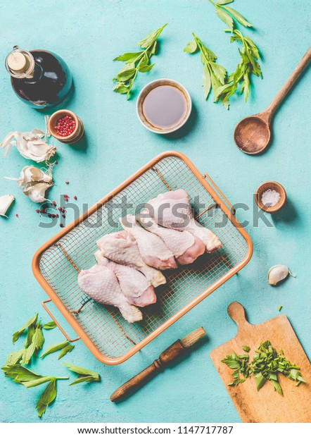 Cooking preparation of raw chicken drumsticks. Raw Chicken legs on grill steel grid with ingredients,  herbs, spices , sauce and cooking spoon on light blue kitchen table background, top view