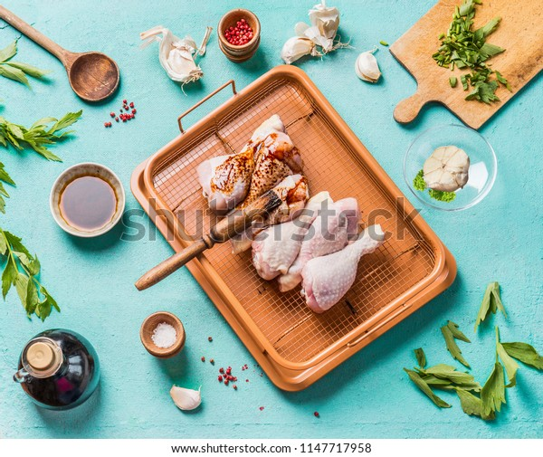 Cooking preparation of raw chicken drumsticks. Raw Chicken legs marinating on plate with ingredients,  herbs, spices , sauce and cooking spoon on light blue kitchen table background, top view