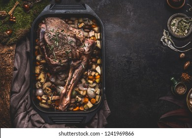 Cooking preparation of venison roast. Leg of deer with bone in cast iron pan with gut vegetables on dark kitchen table background with herbs and spices. Copy space for your recipe or design
