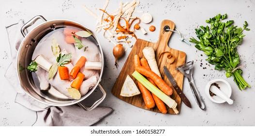 Kochen - Zubereiten von Hühnerbestand (Brot oder Bouillon) mit Gemüse in einem Topf. Küche - grauer Beton-Arbeitsszenerie von oben (Draufsicht, flache Lage).