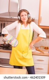 Cooking and preparing food concept. Thinking beauty woman housewife chef with earphones listening music in house kitchen making dinner meal.