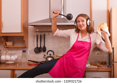 Cooking preparing and making food concept. Modern beauty woman housewife cook chef wearing pink apron and listening music on earphones standing in kitchen.